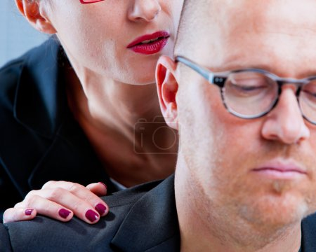 Woman tormenting a man on workplace