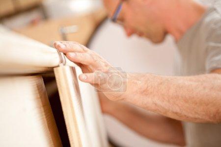 carpenter's hand placing a board