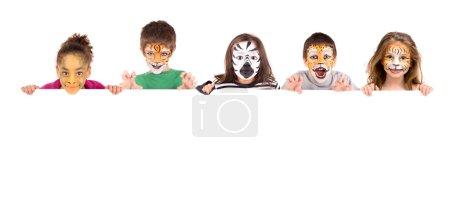 Photo pour Groupe d'enfants avec peinture faciale sur un tableau blanc - image libre de droit