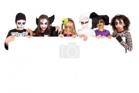 Photo for Kids with face-paint and Halloween costumes over a white board - Royalty Free Image