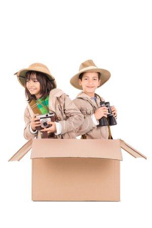 Photo pour Couple d'enfants dans une boîte en carton jouant safari - image libre de droit