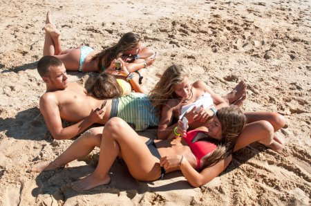 Photo for Group of teenagers in the beach with cellphones - Royalty Free Image