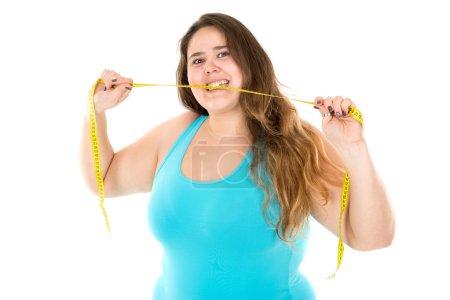 large girl biting a measuring tape