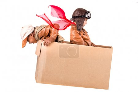 Young boys playing in a cardboard box
