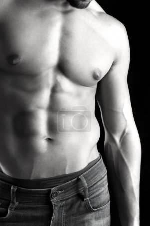 Photo for Ma's torso showing great abdominal muscles over a black background - Royalty Free Image