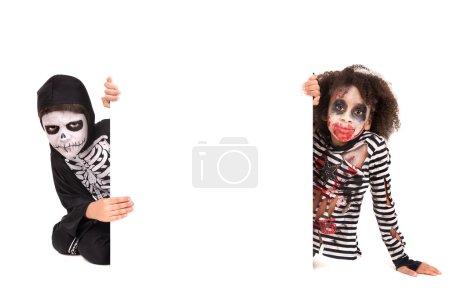 Photo pour Enfants avec peinture sur le visage et costumes d'Halloween sur un tableau blanc - image libre de droit