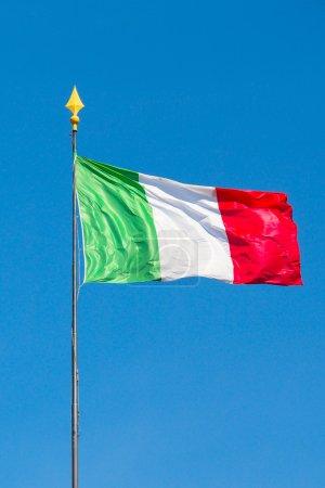 Italian flag waving into blue sky