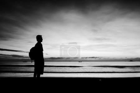 Photo for Silhouette of a man standing at beach in black and white - Royalty Free Image
