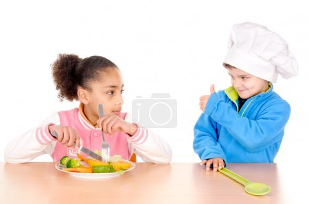 Little boy and girl eating vegetables