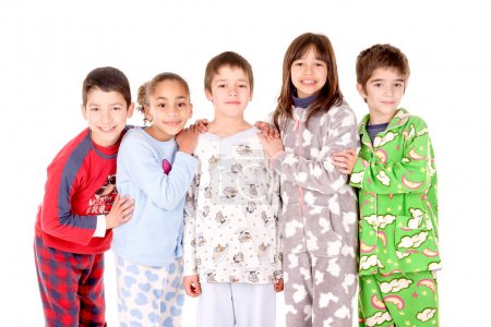 Photo pour Les petits enfants sur leur pyjama dans son lit isolé en blanc - image libre de droit
