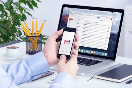 Gmail app on iPhone display in man hands and Macbook Pro screen