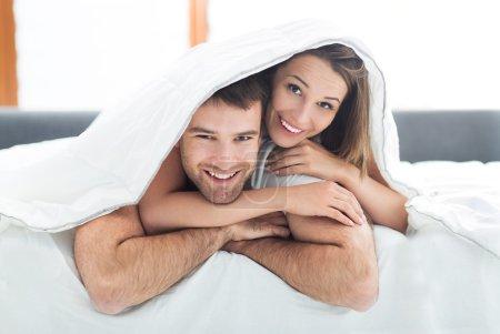 Photo pour Jeune et heureux Couple sous les couvertures de lit - image libre de droit