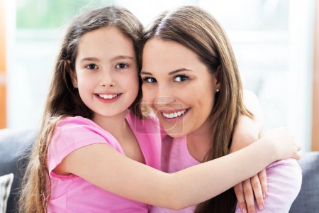 Photo for Happy mother and daughter sitting on sofa and hugging - Royalty Free Image