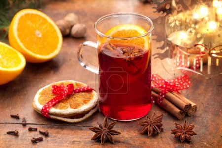 Mulled wine, spices and orange on wooden background