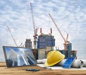 Blueprints und Schutzhelm über einen Tisch in Baustelle
