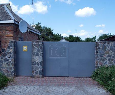 Photo for Iron gates satellite dish fence made of stone - Royalty Free Image