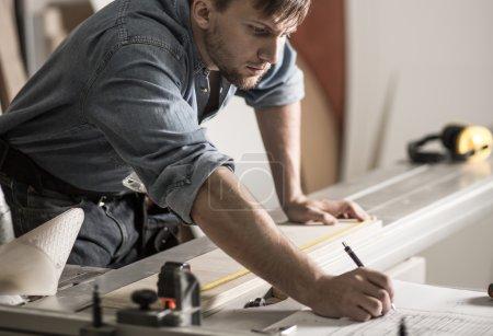 Photo pour Carpenter est en train d'écrire une mesure de planche en bois - image libre de droit