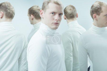 Photo pour Image dupliquée de l'homme avec un problème mental, debout dans l'intérieur blanc - image libre de droit