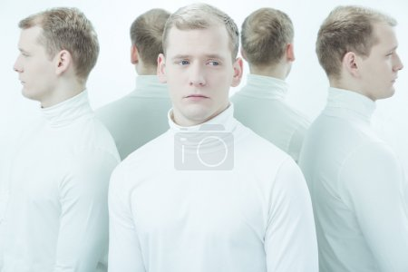 Photo for Sick, young man with split personality standing in white interior - Royalty Free Image