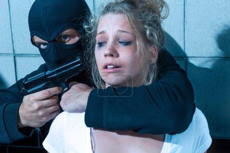 Man pointing gun at girl