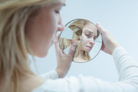 Photo for Close-up of a desolated young woman looking into a broken mirror which she is holding in her hands - Royalty Free Image