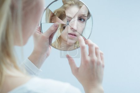 Photo for Young woman touching her own reflection in a broken mirror - Royalty Free Image