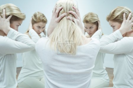 Photo for Anxious young woman in white surrounded by her alter egos - Royalty Free Image