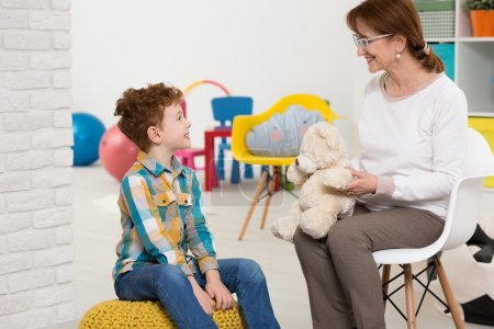 Photo for Elderly nice psychotherapist working with young autistic boy. Sitting in colorful office with toys - Royalty Free Image