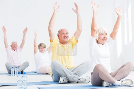 Photo for Senior men and women during fitness classes, stretching their arms while sitting with crossed legs on exercise mats - Royalty Free Image
