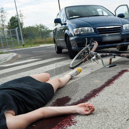 Foto de Un ciclista muerto femenino y un coche en un camino de sangre - Imagen libre de derechos