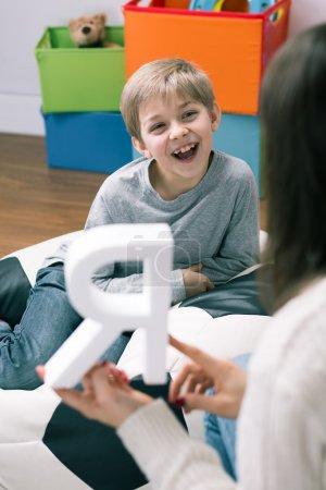 Photo pour Tournage d'un orthophoniste et d'un petit garçon heureux - image libre de droit