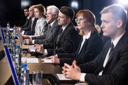 Photo for Several people of different ages sitting at a conference desk with microphones and laptops - Royalty Free Image