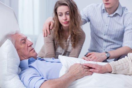 Photo pour Vieil homme couché dans un lit d'hôpital, entouré de ses petits-enfants et de la femme - image libre de droit