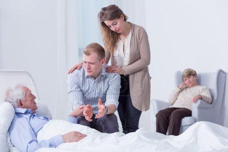 Photo pour Désolée petit-fils parle à son grand-père qui est allongé sur un lit d'hôpital, avec les autres membres de la famille en arrière-plan - image libre de droit