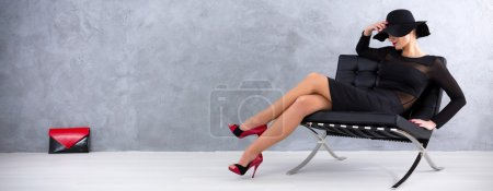 Photo for Sexy woman in black dress with hat and red heels sitting on a lounge chair, red-black handbag in the background - Royalty Free Image