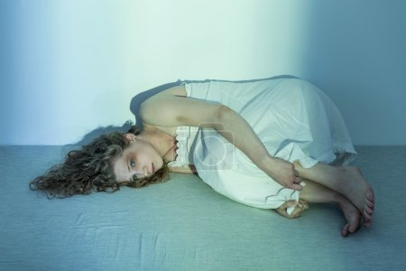 Photo pour Femme engourdie et malheureuse est couchée dans la position foetale sur le sol - image libre de droit