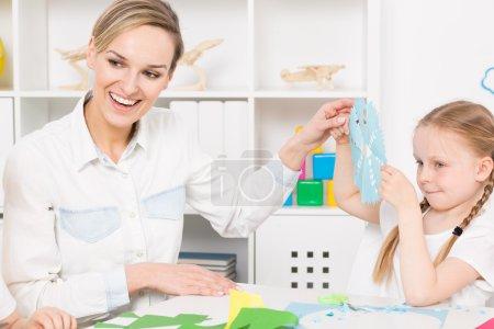Photo pour Professeure maternelle souriante admirant une serviette en papier faite par une petite fille assise à côté - image libre de droit