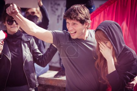 Photo for Young protester with his girlfriend, shouting slogans during a demonstration - Royalty Free Image