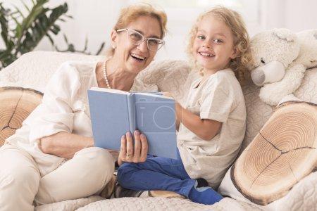 Photo pour Babysitter mature, lisant un livre à un petit garçon - image libre de droit