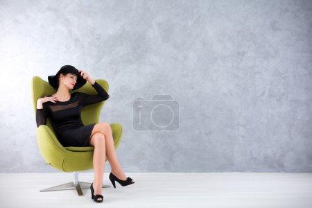 Photo pour Jeune femme séduisante dans une robe noire sexy assise dans une chaise d'oeuf dans une pose ravie - image libre de droit