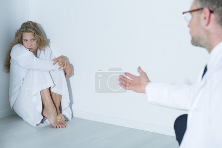 Photo for Shot of a psychiatrist talking to his patient sitting in a corner of a white room - Royalty Free Image