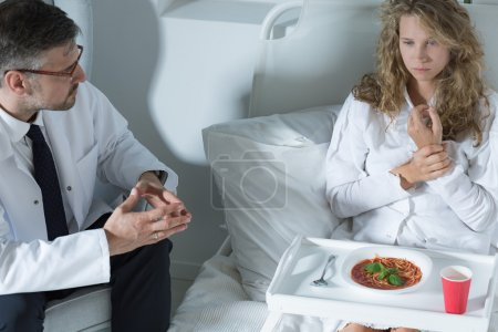 Photo for Shot of a doctor trying to convince his patient to eat a soup - Royalty Free Image