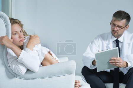 Photo for Shot of a sad young woman sitting in an armchair and her psychiatrist talking to her - Royalty Free Image