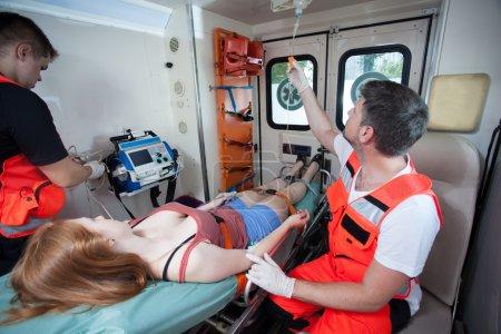 Photo pour Femme blessée et les infirmiers dans une ambulance, horizontale - image libre de droit