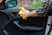 Man cleaning door in a car