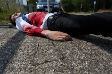 Foto de Hombre muerto en camisa ensangrentada tirado en la calle - Imagen libre de derechos