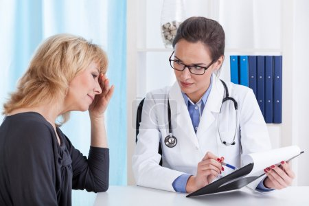 Woman with migraine in doctor's office