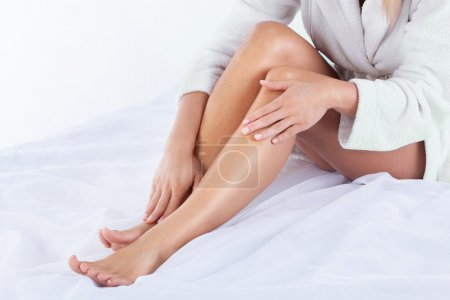 Photo pour Vue horizontale de la femme utilisant une lotion corporelle - image libre de droit