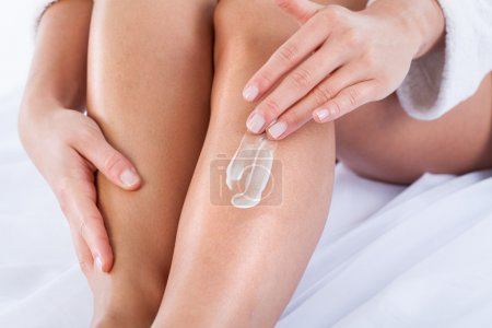Woman applying body lotion on her skin...