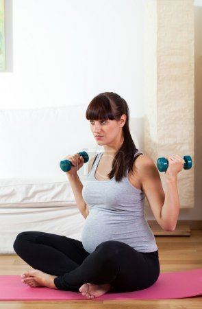 Pregnant girl working out with dumbbells